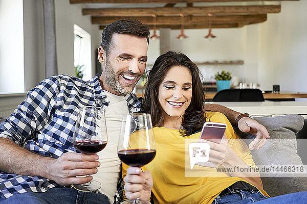 Ehepaar sitzt im Wohnzimmer  trinkt Rotwein und benutzt ein Smartphone