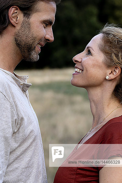 Happy couple in nature  standing face to face  smiling at each other
