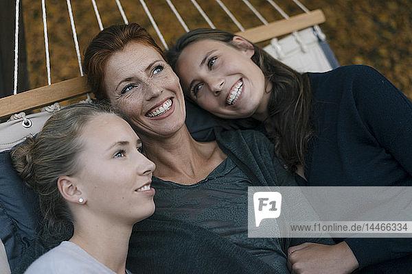 Glückliche Mutter mit zwei Mädchen im Teenageralter  die im Herbst in der Hängematte im Garten liegen