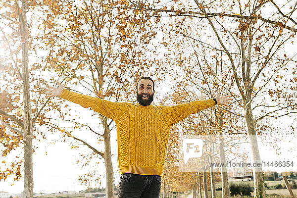Young man with open arms and happy in a park in autumn