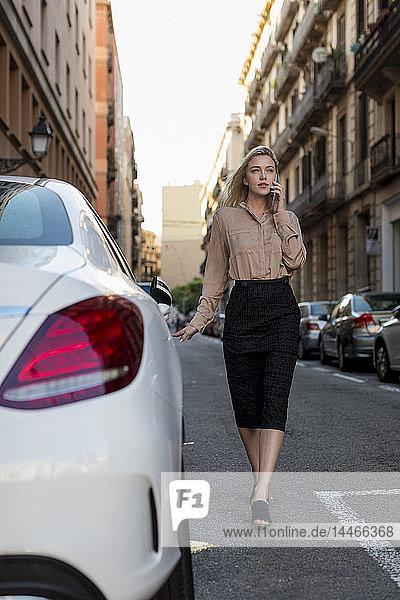 Junge Geschäftsfrau am Handy in der Stadt unterwegs
