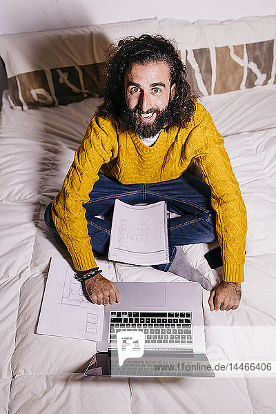 Portrait of happy young man working in bed at home with laptop and documents