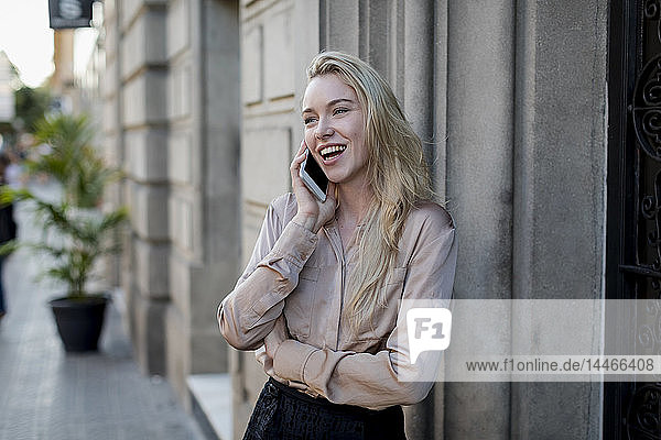 Happy young businesswoman on cell phone in the city