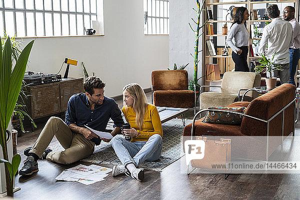 Geschäftsmann und Geschäftsfrau besprechen Dokumente im Loft-Büro