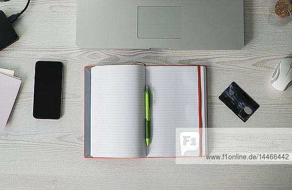 Bürotisch mit Smartphone  aufgeklapptem Notebook  Laptop und Kreditkarte  Draufsicht