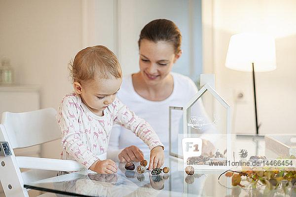 Mutter und kleine Tochter basteln zu Hause an herbstlich dekorativem Haus