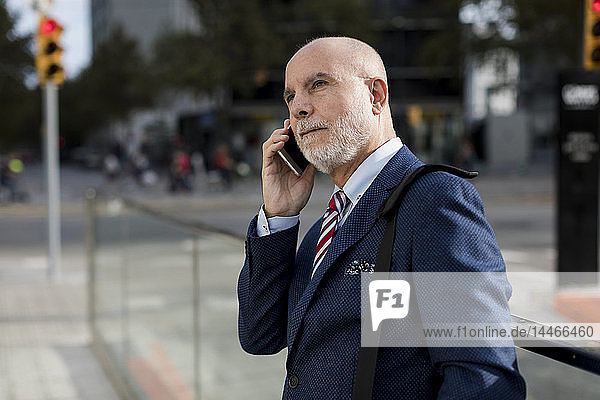 Senior businessman talking on cell phone in the city