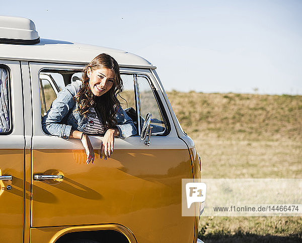 Pretty woman on a road trip with her camper  looking out of car window