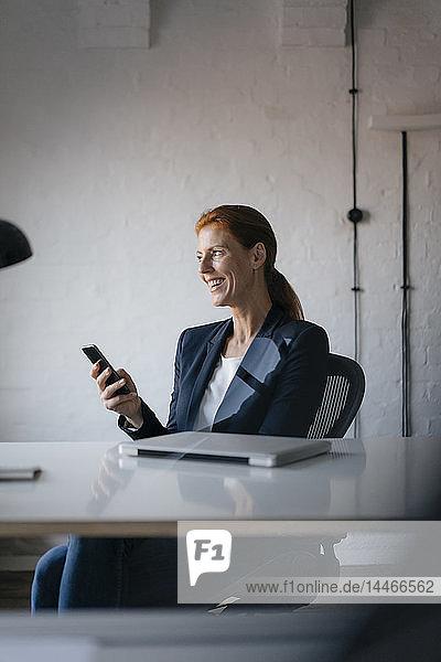 Glückliche Geschäftsfrau mit Handy am Schreibtisch im Büro