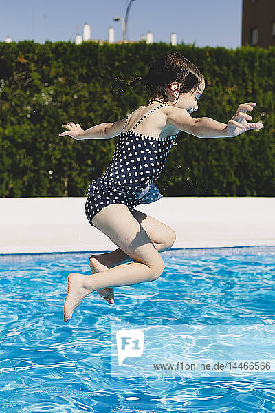 Happy little girl jumping into swimming pool