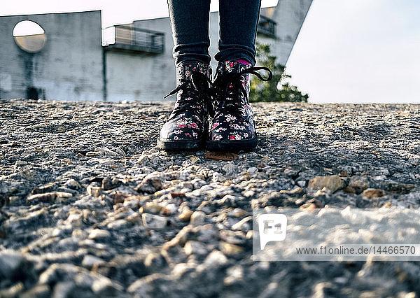 Mädchen trägt Stiefel mit Blumenmuster