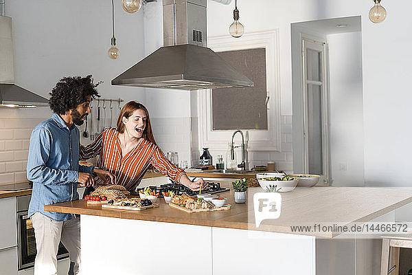 Paar steht in der Küche und bereitet ein Abendessen vor