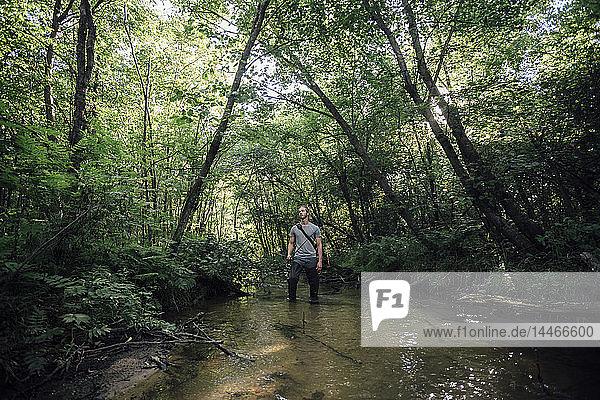 Junger Mann beim Angeln in einem Wald