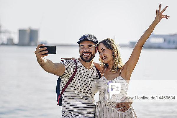 Spanien  Andalusien  Malaga  glückliches Touristenpaar  das sich an der Küste mit einem Smartphone selbstständig macht