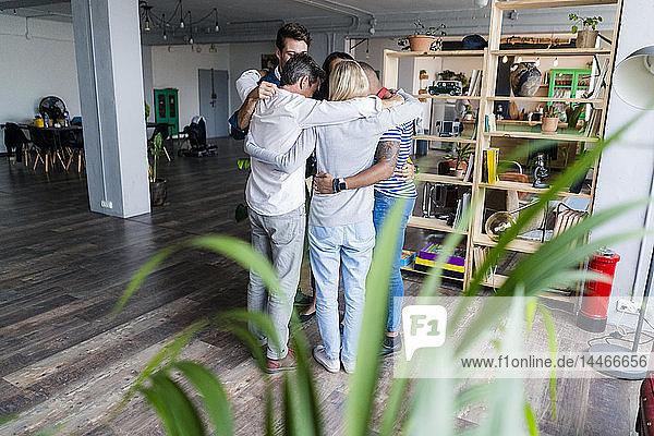 Business team huddling in loft office