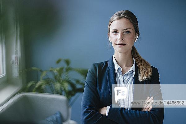 Porträt einer jungen Geschäftsfrau mit verschränkten Armen und Ohrknöpfen