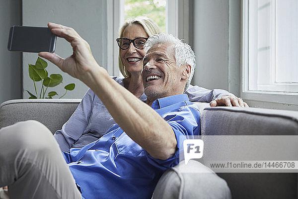 Glückliches reifes Paar  das zu Hause auf der Couch sitzt und sich ein Selfie