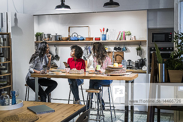 Three women talking at table in a loft