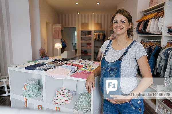 Portrait of smiling pregnant woman in a boutique for baby clothing