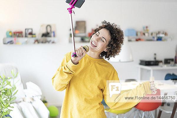 Sorglose Frau singt zu Hause in ein Mikrofon,  das an einem Selfie-Stock befestigt ist