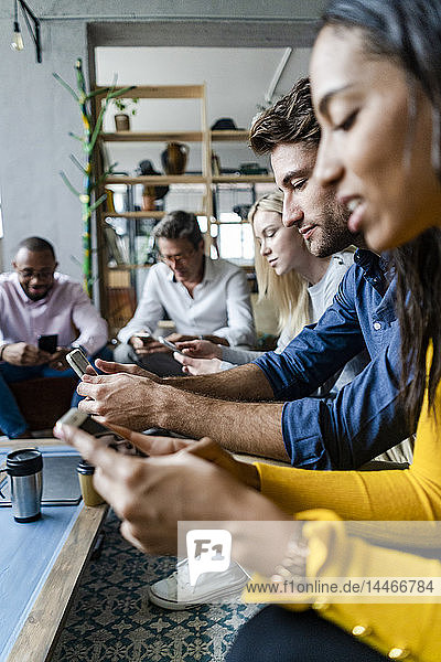 Business team sitting in loft office using cell phones