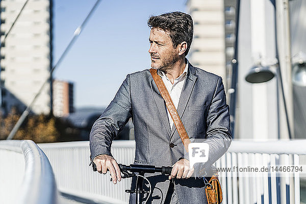 Mature businessman commuting in the city with his kick scooter