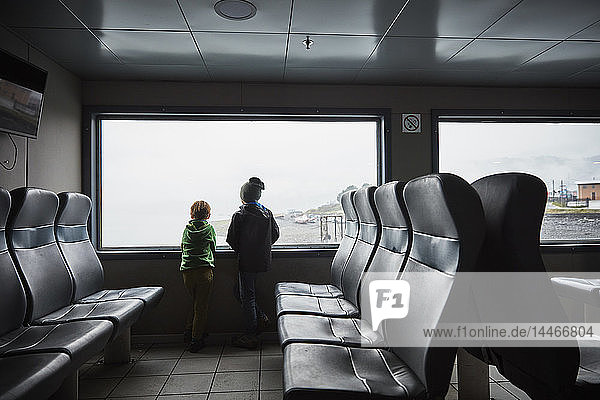 Chile  Puerto Montt  two boys looking out of window of a ferry
