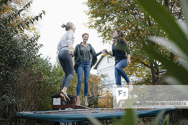 Glückliche Mutter mit zwei Mädchen im Teenageralter  die im Herbst im Garten auf dem Trampolin springen