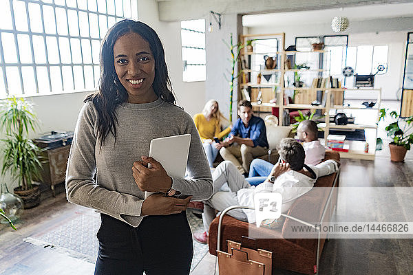 Portrait of smiling young businesswoman with coworkers in background in loft office