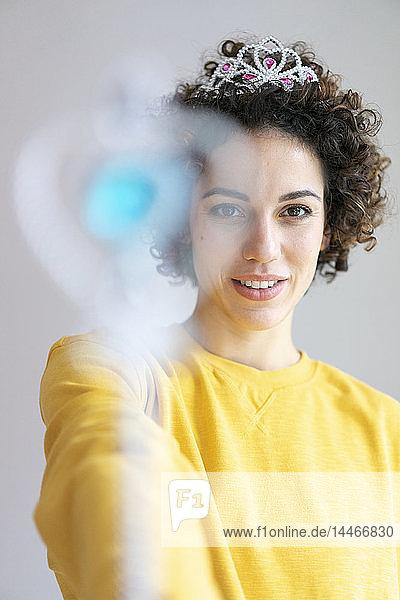Porträt einer lächelnden Frau mit Diadem und Zauberstab