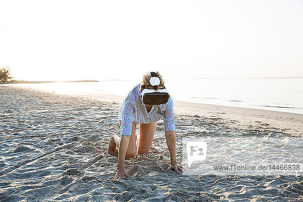 Thailand  woman using virtual reality glasses on the beach in the morning light