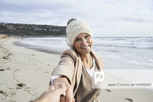 Spain  Menorca  portrait of happy senior woman holding hand on the beach in winter