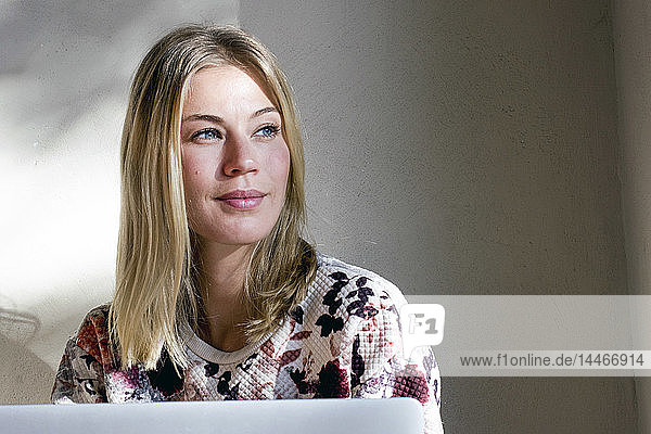 Portrait of blond woman with laptop in a cafe looking at distance