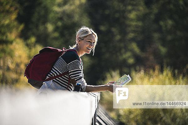 Österreich  Alpen  glückliche Frau auf einer Wanderung mit Karte auf einer Brücke