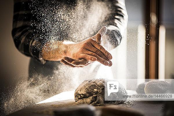 Mann bereitet in der Küche schwarze Burgerbrötchen zu