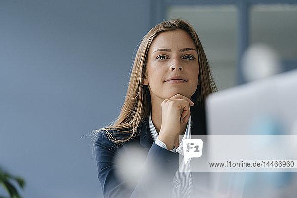 Porträt einer jungen Geschäftsfrau  die im Büro arbeitet und einen Laptop benutzt