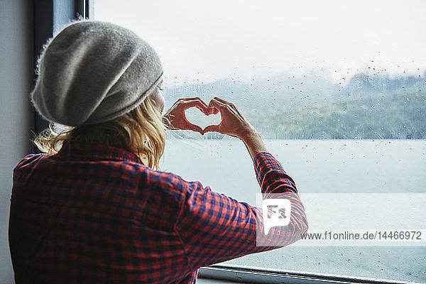 Chile,  Hornopiren,  Frau,  die mit ihren Händen am Fenster einer Fähre ein Herz formt