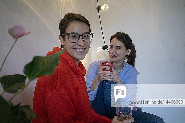 Zwei Freundinnen zu Hause sitzen in der Küche  unterhalten sich und trinken Tee