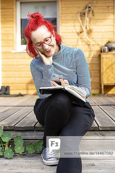 Porträt einer lächelnden älteren Frau mit rot gefärbten Haaren  die mit ihrem Handy auf der Terrasse vor ihrem Haus sitzt