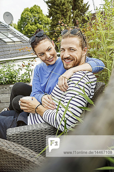 Young couple relaxing on their balcony,  sitting on couch