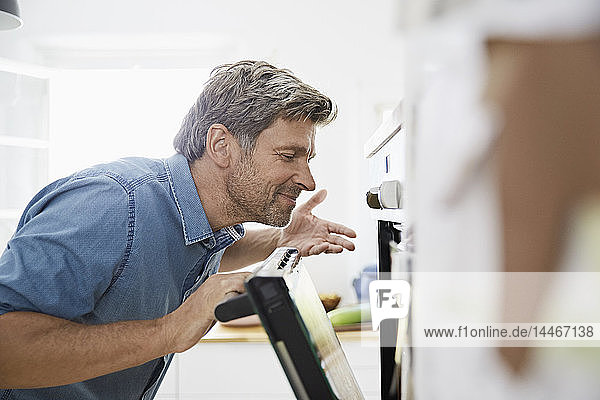 Mature man in his kitchen smelling meal in the oven