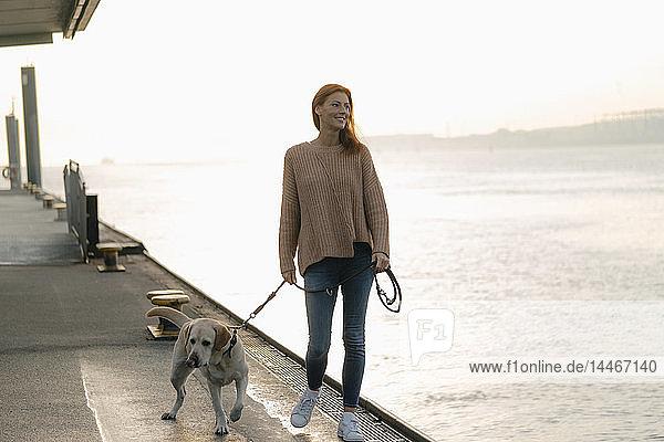 Deutschland  Hamburg  Frau beim Spaziergang mit Hund auf der Mole am Elbufer