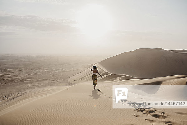 Namibia  Namib  back view of woman standing on desert dune looking at view