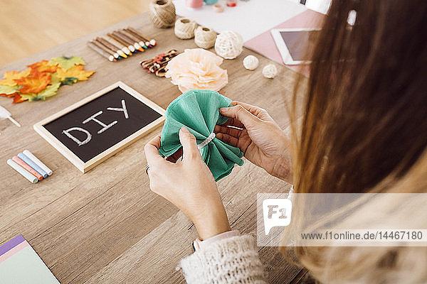 Junge Frau bastelt in ihrem Atelier mit Papierblumen