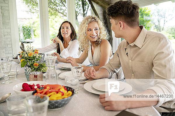 Junger Mann und Frau flirten auf einer Familienfeier