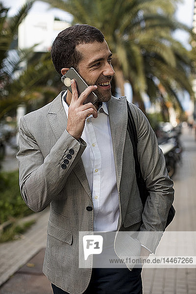 Happy businessman in the city talking on cell phone
