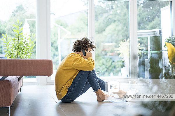 Frau benutzt Laptop und Mobiltelefon zu Hause