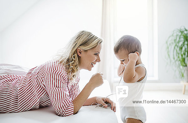Smiling mother and toddler son with earphones in bedroom at home