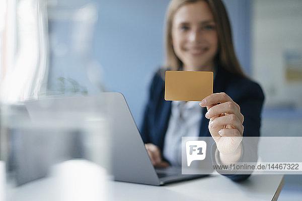 Junge Geschäftsfrau macht Online-Zahlungen und zeigt ihre Kreditkarte
