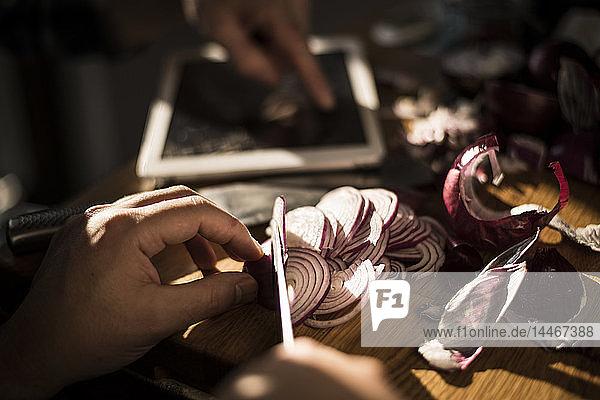 Hände beim Zwiebelschneiden